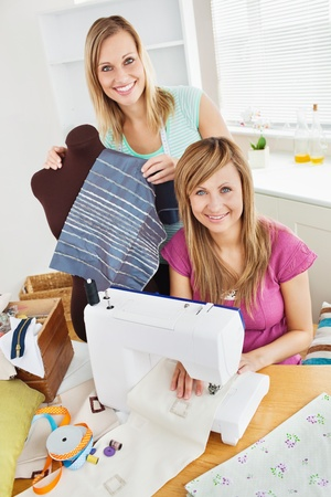 Bright young female friends sewing clothes together at home photo