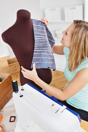 Serious young woman sewing clothes at home photo