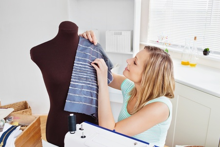 Delighted young woman sewing clothes at home photo