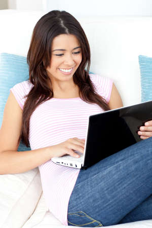 wireless: Beautiful asian woman using her laptop lying on the sofa in the living-room