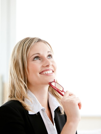delighted: Thoughtful young businesswoman holding glasses