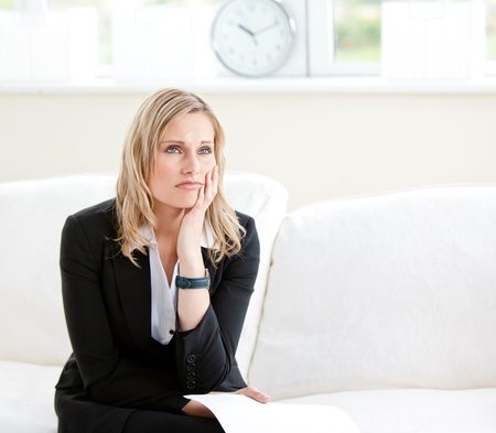 Dejected businesswoman holding a paper and sitting on a sofa photo