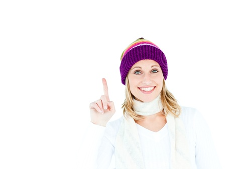 Joyful woman with a colorful hat pointing upwards photo