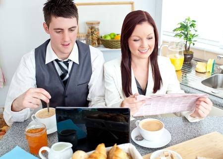 Joyful couple of businesspeople having breakfast in the kitchen Stock Photo - 10242852