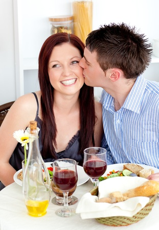 cheeks: Handsome boyfriend giving a kiss to his attractive girlfriend during dinner Stock Photo