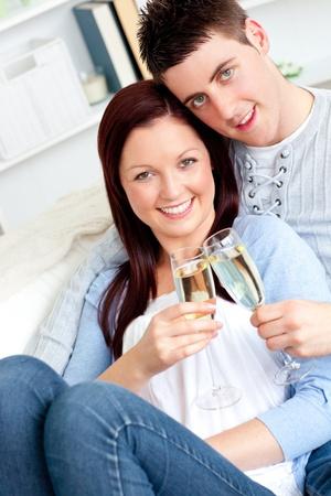 Loving couple drinking on a sofa Stock Photo - 10243406