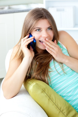 answering the phone: Merry woman talking on phone sitting on a sofa