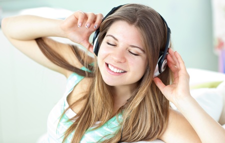 Delighted woman listening to music with headphones on a sofa photo