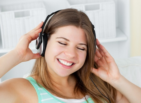 Cheerful young woman listening to music with headphones on a sofa photo