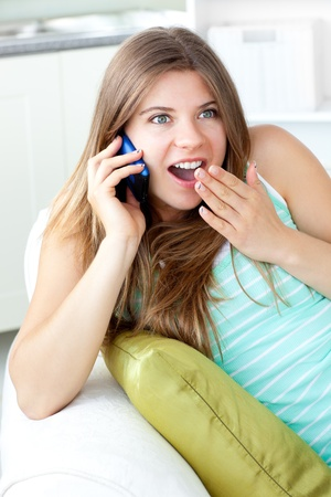 Surprised woman talking on phone lying on a sofa in the living-room photo