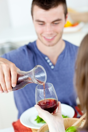 Cute man dining with his girlfriend at home serving her wine photo