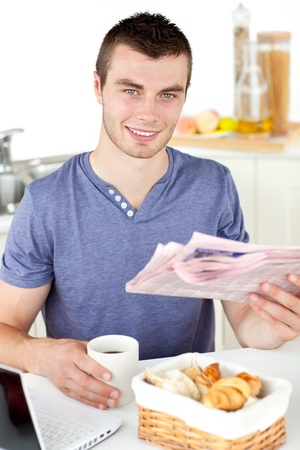 Positive young man holding a cup and a newspaper smiling at the camera sitting in the kitchen photo