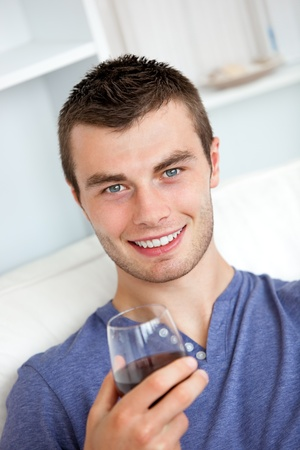 Animated young man drinking wine looking at the camera sitting on the sofa photo