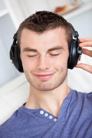 Lively young man listening to music sitting on the couch in the living-room photo