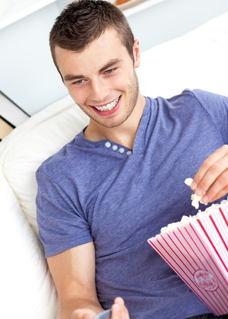 Positive caucasian man holding a remote and eating popcorn in the living-room photo