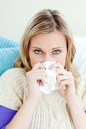 poorly: Morbid woman using a tissue sitting on a sofa at home