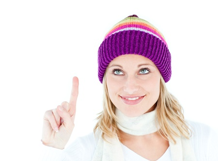 Pretty woman with a colorful hat pointing upwards photo