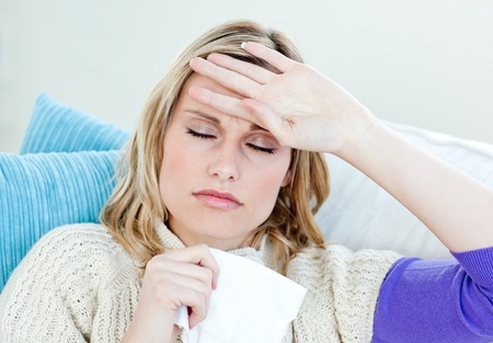 Sick woman with headache lying on the sofa in the living-room photo