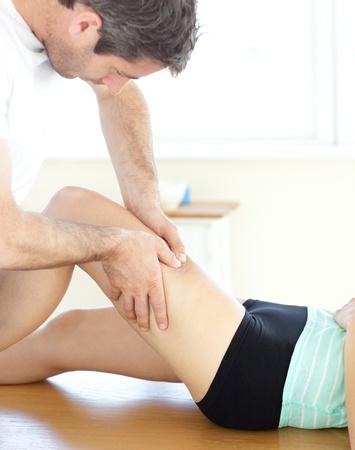 massage jambe: Beau jeune physioth�rapeute donnant un massage des jambes Banque d'images