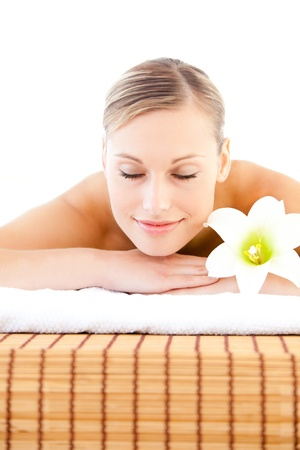 Close-up of a delighted woman lying on a massage table with a flower photo