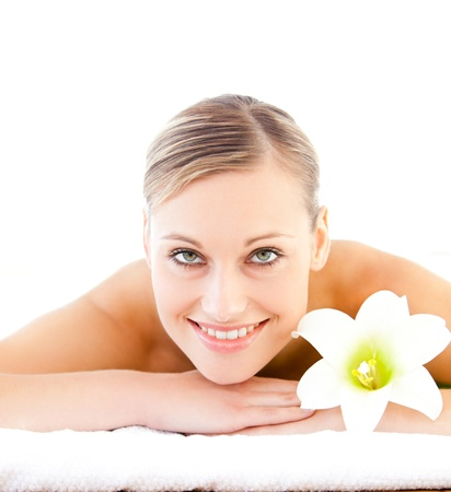 Close-up of a positive woman lying on a massage table with a flower photo