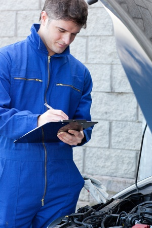 Handsome mechanic writing on a clipboard standing in front of a car photo