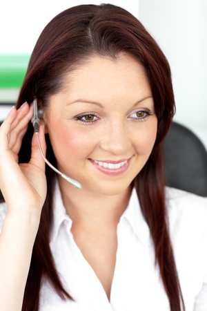 Positive young businesswoman sitting at her desk and wearing earpiece photo
