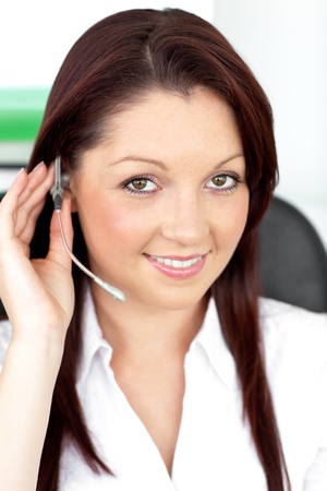 Attractive young businesswoman wearing earpiece in a customer service photo