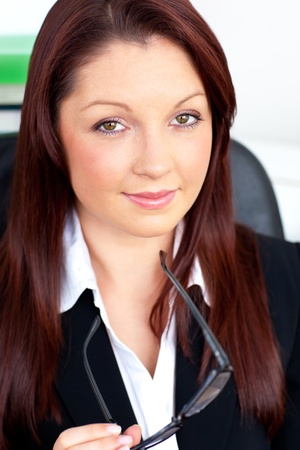 Charismatic businesswoman holding her glasses sitting in her office photo