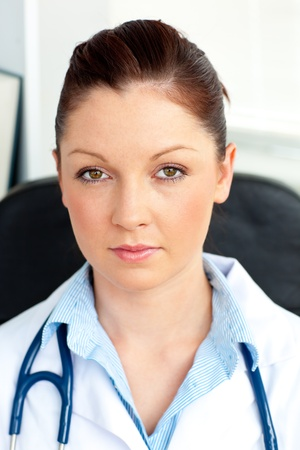 Serious female doctor smiling at the camera sitting photo