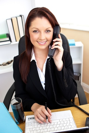 Self-assured businesswoman talking on phone and using her laptop at her desk photo