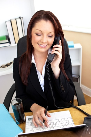 Concentrated businesswoman talking on phone and using her laptop at her desk photo