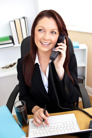 Assertive businesswoman talking on phone and using her laptop at her desk photo