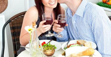 diner romantique: Close-up og un ami joyeux embrasser sa belle amie pendant le d�ner