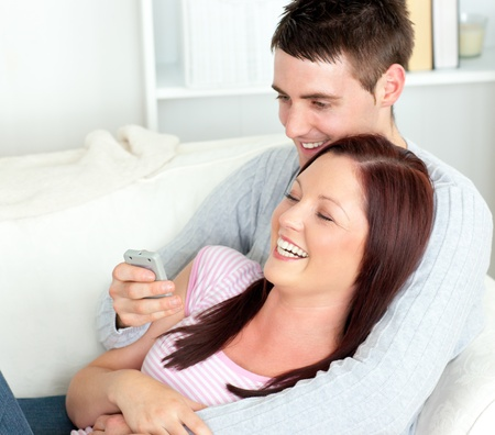 Portrait of an embracing couple watching television lying on the sofa Stock Photo - 10241834