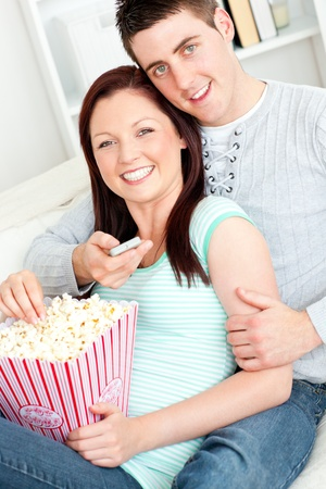 Hugging couple eating popcorn and watching television on the sofa photo