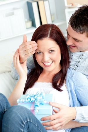 Surprised girlfriend being offered a present by her boyfriend in the living-room photo