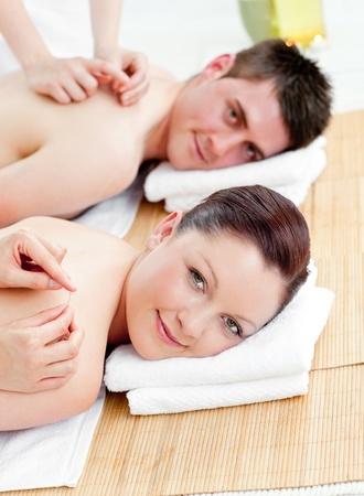Charming caucasian couple receiving a back massage photo