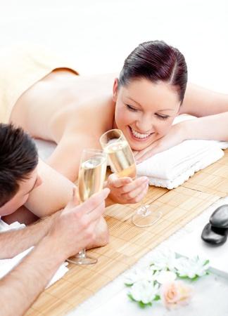 homme massage: Aimer le champagne jeunes potable couple allong� sur une table de massage