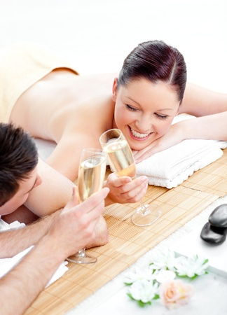 couples therapy: Loving young couple drinking champagne lying on a massage table
