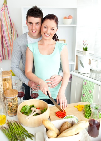 Enamored young couple cutting vegetables in the kitchen photo