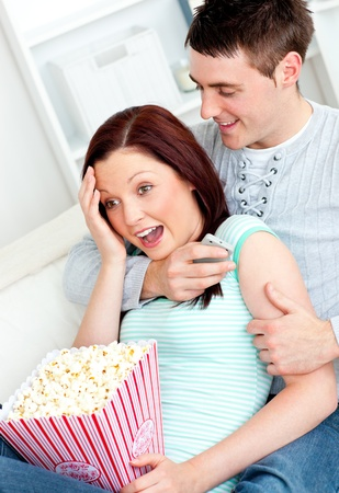 Young couple lying on the sofa with popcorn and remote photo