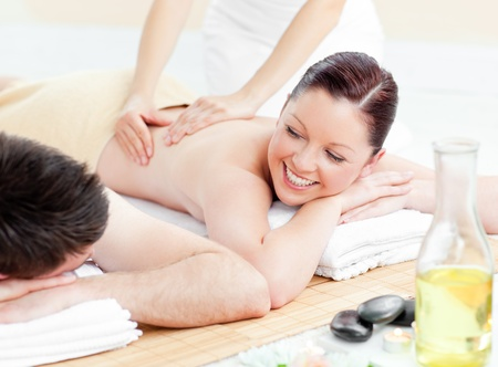 Glowing young couple receiving a back massage photo