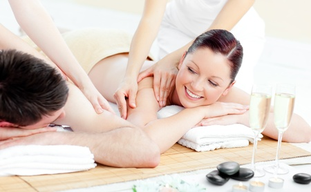 Positive young couple enjoying a back massage photo