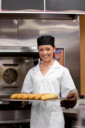 haciendo pan: Baker joven sonriente con baguettes