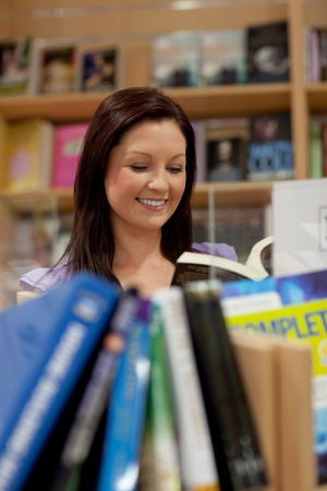 Pretty young woman reading a book Stock Photo - 10242533