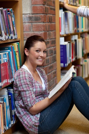 Smiling young woman reading a book sitting on the floor photo