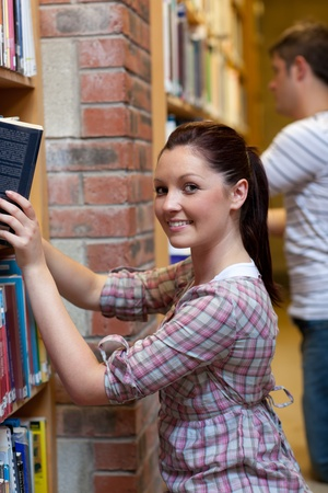 Charming young woman looking for a book photo