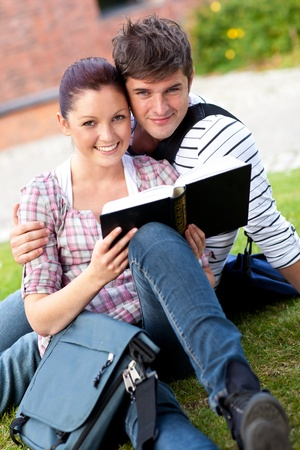 Smiling couple of students reading a book sitting on grass photo