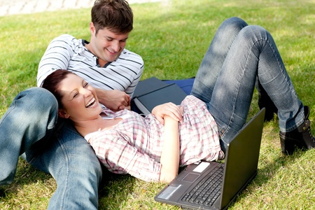 Couple of bright students using a laptop lying on the grass photo